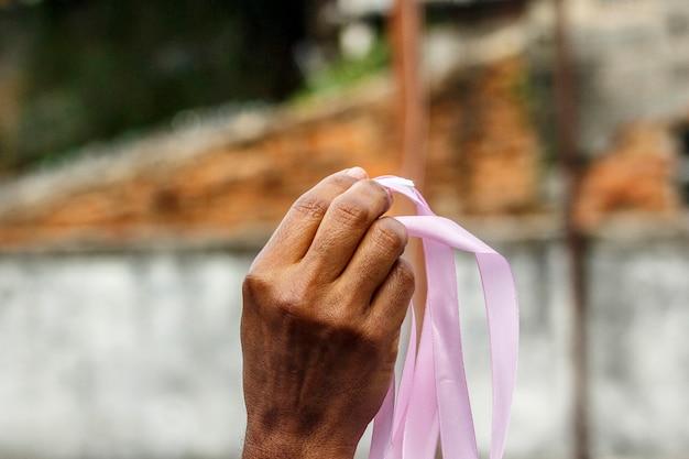 Main d'une femme noire tenant un ruban rose faisant du champagne pour la prévention du cancer du sein à rio de janeiro.