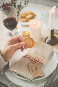Main de femme non reconnaissable tenant un biscuit contre une table dressée pour le dîner de noël