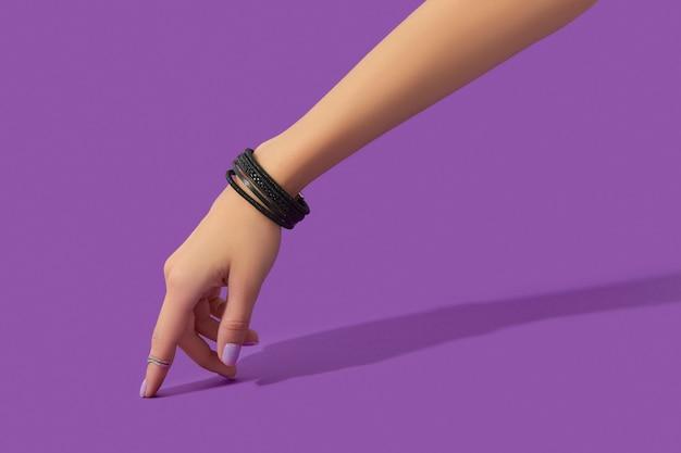 Main de femme avec des ongles de couleur pastel à la mode sur fond violet concept de vente de mode shopping