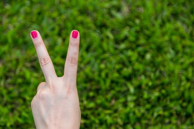 Main de femme avec des ongles rouges montrent signe de paix ou numéro deux avec deux doigts sur fond d'herbe verte