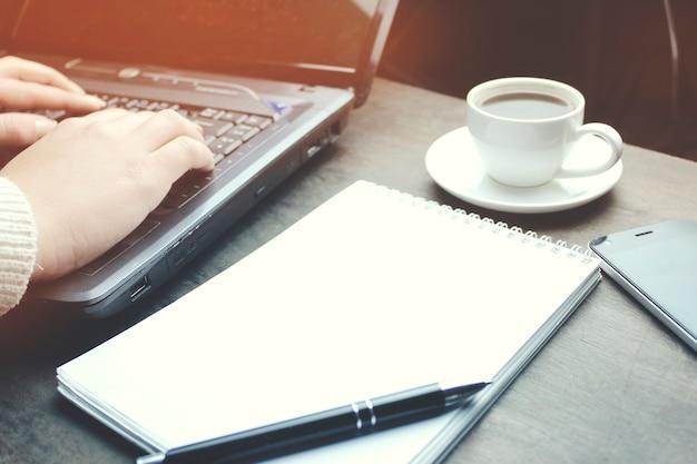 Main de femme sur ordinateur avec un téléphone, une tasse de café et un bloc-notes