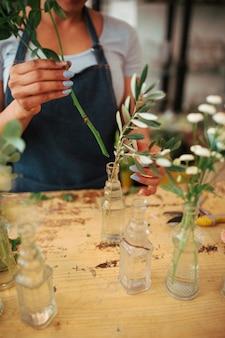 Main de femme organisant des plantes dans un vase de verre sur le bureau