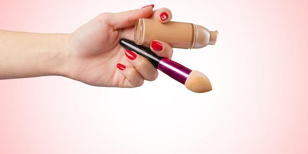 Main de femme avec un outil cosmétique de fondation