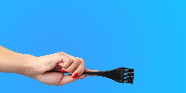 Main de femme avec des outils et accessoires de coiffeur isolés sur bleu