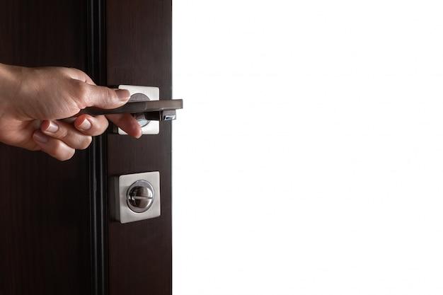 La main de la femme ouvre la porte en bois noir