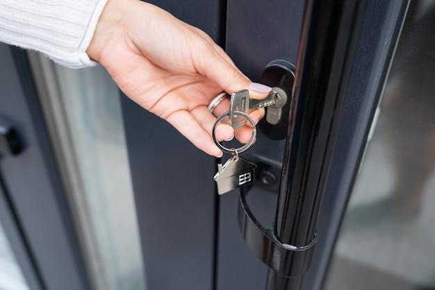 La main d'une femme ouvre la porte avec une clé sur laquelle le porte-clés est suspendu à la maison et copie l'espace.