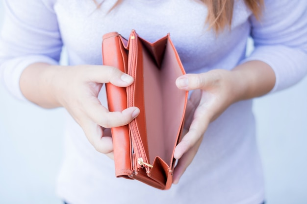 Main femme ouvrir un portefeuille vide