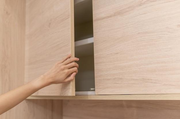 Main de femme ouvrir les portes de placards en bois.