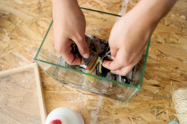 Main de femme avec des papiers déchirés dans un récipient en verre