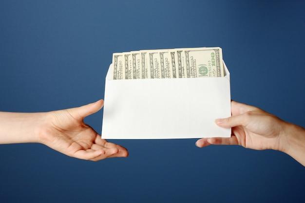 La main de la femme passe l'enveloppe avec le salaire sur fond bleu