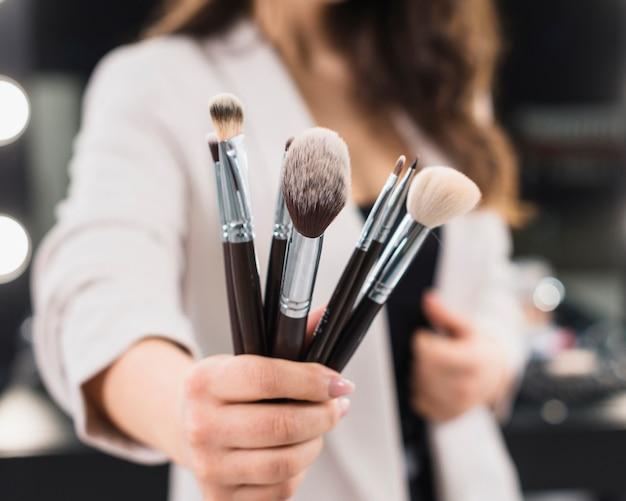 Main de femme avec des pinceaux de maquillage
