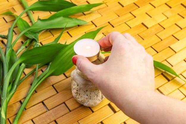 Main de femme plaçant une bougie d'éclairage sur une pyramide de pierre blanche avec des feuilles de bambou sur un tapis en bois