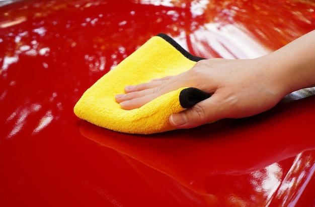 Main de femme polir le capot de voiture rouge avec une serviette jaune après l'épilation