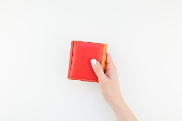 Main de femme avec portefeuille rouge isolé