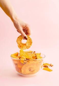 Main de femme prenant l'anneau d'ananas dans un bol avec un assortiment de fruits séchés.