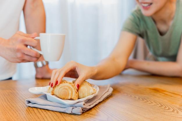 Main de femme prenant des collations au curry puff avec un ami tenant une tasse de café à la maison.