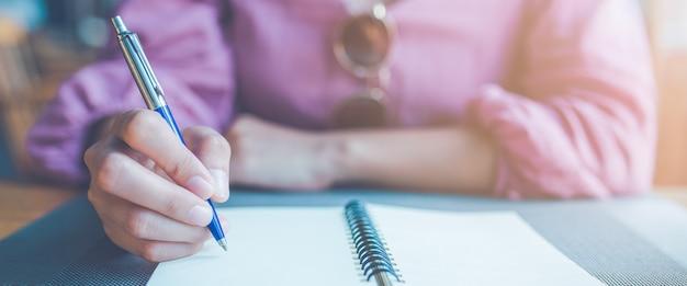 Main de femme prenant des notes sur un ordinateur portable à l'aide d'un stylo.