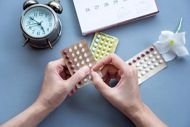 Main de femme prenant des pilules contraceptives orales
