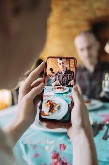 La main d'une femme prenant un portrait de son assiette de nourriture et de son partenaire.