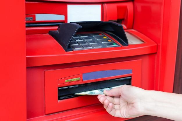 Une main de femme prend de l'argent en dollars américains d'un distributeur automatique de billets rouge