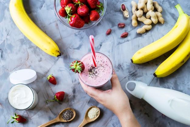 Une main de femme prend un verre de smoothie fraise banane parmi les ingrédients