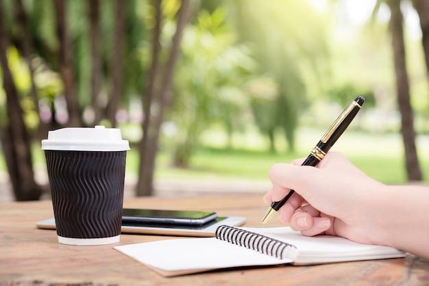 Main de femme prendre des notes avec un stylo sur un ordinateur portable et boire un café