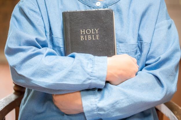 Main de femme avec la prière de la bible, mains jointes en prière sur une sainte bible dans le concept de l'église pour la foi, la spiritualité et la religion.
