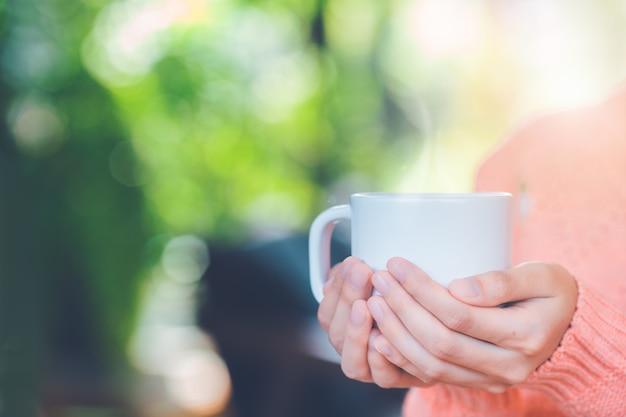 Main de femme en pull chaud tenant une tasse de café.