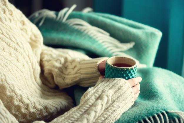 Main de femme en pull en laine tenant une tasse de thé au citron par une journée froide. espace de copie. concept de vacances d'hiver et de noël.