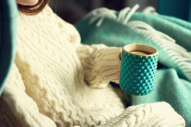 Main de femme en pull en laine tenant une tasse de thé au citron par une journée froide