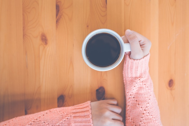 Main de femme en pull rose chaud tenant une tasse de café.