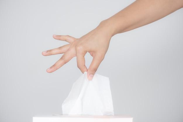 Main de femme ramassant du papier de soie blanc dans une boîte à mouchoirs sur fond gris