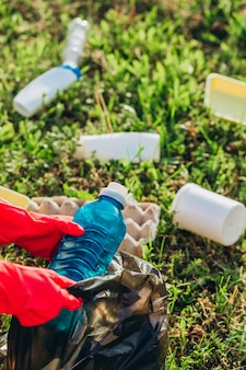 Main de femme ramasser des déchets en plastique pour le nettoyage au parc.