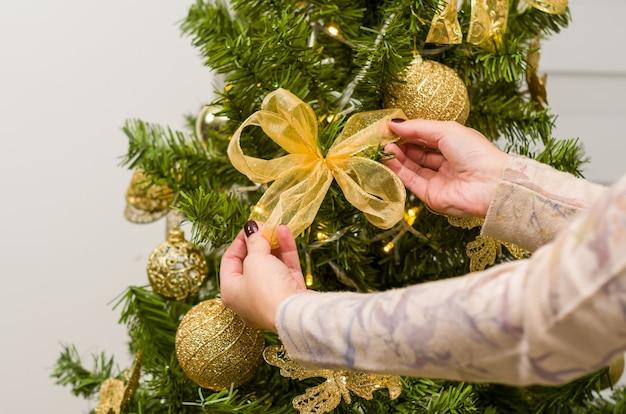 Main de femme ranger et décorer l'arbre de noël