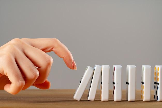 Main de femme renversant des pièces de domino