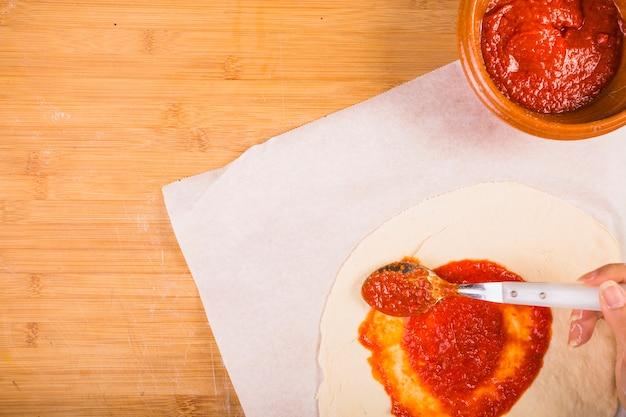 Main de femme répandre la sauce sur la pâte