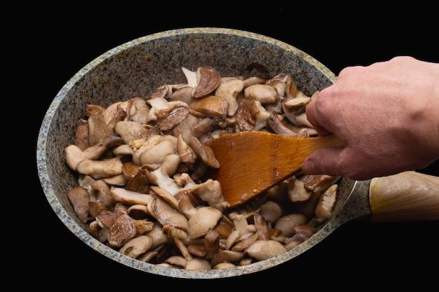 La main d'une femme retourne une cuillère en bois de champignons frits ou cuits dans une poêle à frire sur fond noir. concept d'alimentation saine, régime alimentaire végétarien