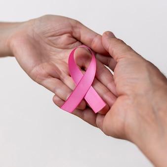Main de femme avec ruban rose et main d'homme soutenant la campagne de sensibilisation au cancer du sein d'octobre rose