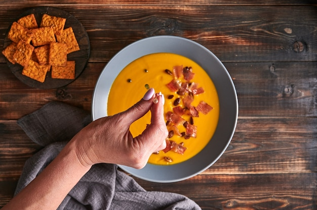 La main de la femme s'égoutte de l'huile verte d'une pipette sur la soupe traditionnelle à la crème de purée de citrouille avec des carottes