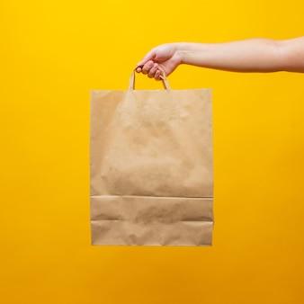 La main d'une femme avec un sac en papier sur fond jaune