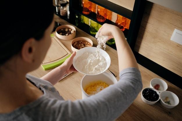 Main de femme saupoudrant de farine dans un bol blanc