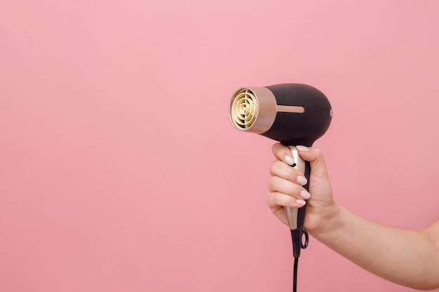À la main de femme sèche-cheveux sur mur rose