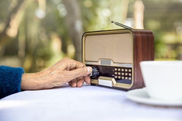 Main de femme senior tournant le bouton sur la radio vintage dans la cour.
