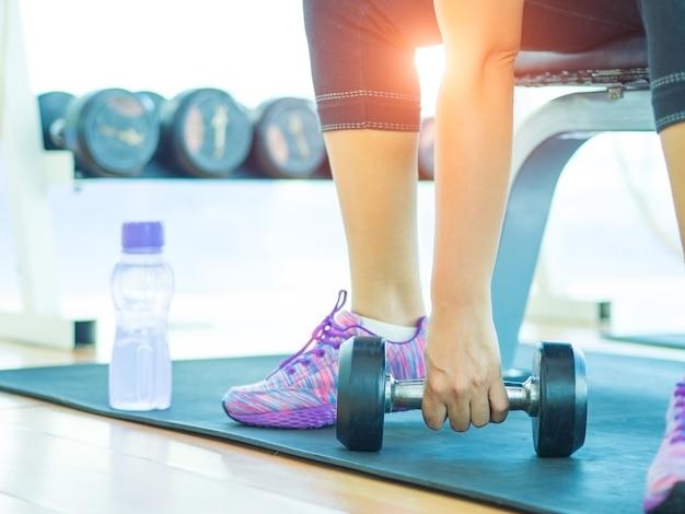 Main de femme soulevant des haltères dans le gymnase avec des équipements de fitness backgroound