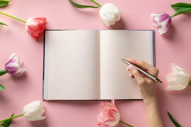 Main de femme avec un stylo et un cahier vierge sur fond rose avec un cadre de fleurs colorées.