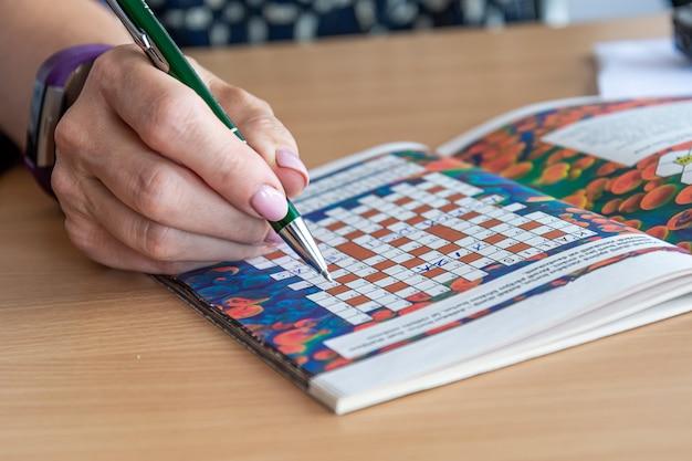 Une main de femme avec un stylo écrit des solutions à un puzzle de mots croisés, gros plan, concept d'entraînement de l'esprit
