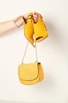 Main de femme tenant des accessoires de mode féminine jaune, des chaussures et un sac à main.
