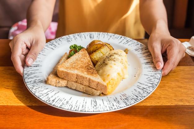 Main de femme tenant une assiette blanche avec omelette, pomme de terre, tomates, persil et fromage feta