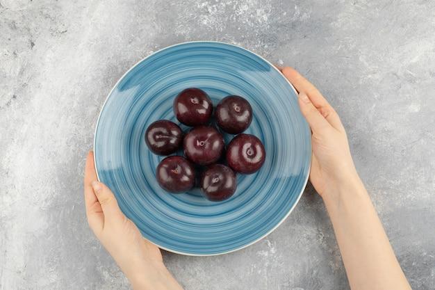 Main de femme tenant une assiette de prunes fraîches sur une surface en marbre.