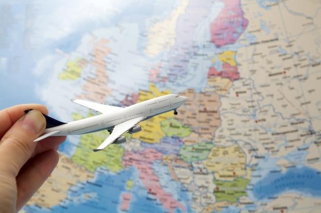 Main de femme tenant un avion sur fond de carte